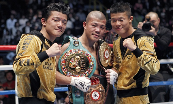 Koki Kameda of Japan, center, donning the newly-captured champion belt, green, in addition to the two he already has, poses with his younger brothers Daiki, left, and Kazuki after Koki's victory over Alexander Munoz of Venezuela in their 12-round WBA bantamweight world title boxing bout in Saitama, Japan, Sunday, Dec. 26, 2010. Koki Kameda won a unanimous decision over Munoz to take the vacant title. (AP Photo/Shizuo Kambayashi)